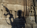 The Silhouetted Shadow of a Man Holding an Automatic Rifle is Cast against a Cambodian Temple Wall