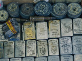 A Tray Full of War Memorabilia Engraved Zippo Lighters  Dog Tags  Bullets  and Ancient Coins