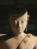 A Statue of Buddha with Eyes Shut Stands in Half Shadow