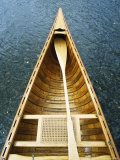 The Bow and Oar of a Handmade Wooden Canoe Resting in Water Papier Photo par Bill Curtsinger