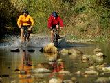 Mountain Bikers Enter a Rocky Stream