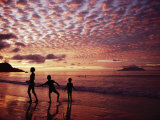 Sunset Reddens a Cloudy Sky as Silhouetted Children Play on the Beach