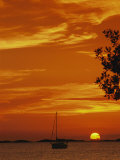 A Sailboat is Silhouetted by a Brilliant Orange Sunset