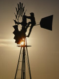 A Man Climbs a Windmill to Make Adjustments