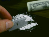 A Hand Dividing up a Pile of Cocaine with a Razor Blade
