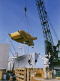 A Ship Being Loaded with Farm Equipment