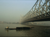 A Man Guides a Boat under a Bridge on the Hooghly River at Calcutta