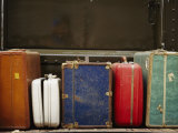 Colorful But Worn Luggage Awaits Travelers in a Train Station