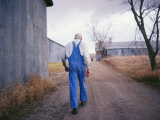 An Elderly Farmer in Overalls Walks Along a Dirt Road Past a Barn