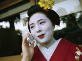 A Kimono-Clad Geisha Talks on a Cell Phone