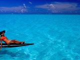 Woman Basking in the Sun on an Outrigger Boat in an Island Lagoon  Huahine Iti  French Polynesia