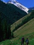 Trekkers Walk Between the Kol-Say Lakes with the Alatau Mountains Behind  Kazakhstan