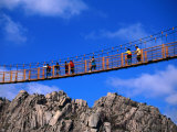 Hikers Crossing Steel Suspension Bridge Over Crevasse  Wolchulsan National Park  South Korea