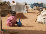 A Girl Washes Plates for Her Family in the North Darfur Refugee Camp of El Sallam October 4  2006