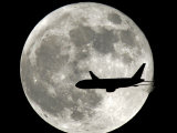A Jet Plane Passes in Front of the Full Moon Above Surfside  Fla