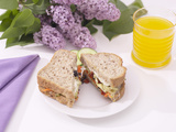 Sandwich and Juice on Table with Purple Flowers