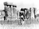 A Naked Hippy Watches Stonehenge from Behind Barb Wire on Summer Solstice