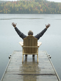 Man Sitting on a Dock with Arms Outstretched