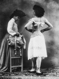 Lady Tries on a Corset While Another Woman Waits with Another One