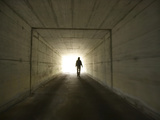 Person Walking Through Tunnel Towards Light