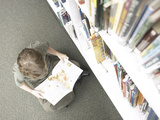 Little Boy Reading Book Beside Library Shelf