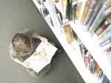 Little Boy Reading Book Beside Library Shelf