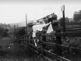 Two Children Stand on a Fence and Wave a Handkerchief at a Passing Steam Train