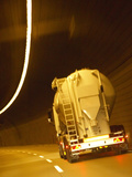 White Tanker Truck Driving Through Tunnel Lit with Electrical Lighting