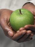 Man in White Shirt Holding Green Apple