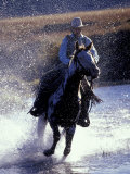 Cowboy on Horseback Galloping through River  Ponderosa Ranch  Seneca  Oregon  USA