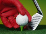 Gloved Hand Placing Golf Ball on Tee