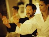 Mature Man Teaching a Young Woman Martial Arts
