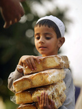 A Boy Carries Rusk as He Assists Others to Send a Consignment of Relief Supplies to Uri