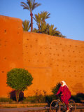 Veiled Woman Bicycling Below Red City Walls  Marrakech  Morocco