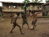 A Group of Panamanian Youths Slide Through the Mud During a Pick-Up Game of Soccer