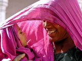 A Woman Shields Her Child from the Sun Using Her Scarf