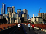 Women Jogging Across Stone Arch Bridge with City Skyline Beyond  Minneapolis  USA