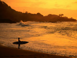 Surfer Standing at Waimea Bay at Sunset  Waimea  USA