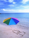 Umbrella on the Beach with Hearts Drawn in the Sand