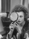 Actress Hanna Schygulla Looking in Hand Mirror While Applying Makeup