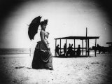 Georgiana Parker  in a Dress and Hat  Carrying a Parasol with a Group People at the beach
