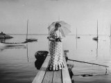 Young Woman  Dressed in a Print Dresses Standing on a Boat Landing by a Body of Water