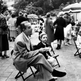 Vincente Minnelli with coffee sitting in chair with Daughter Liza at Outdoor Children's Party Being