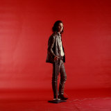 Rock Star Jim Morrison of the Doors Standing Alone Next to Microphone in Front of a Red Backdrop