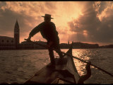 Gondolier  Against Sun and Cityscape  Standing on Front of Gondola Moving Away From Campanile