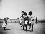 Sweetly Dressed Girls Jumping Rope Together  as Nearby Toddler with Parasol Looks On  at Ft Greene