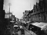 Bustling View of Fulton St  with Rows of Shops and Horse Drawn Carriages