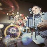 Architect/Designer Charles Eames with Engine that Generates Solar Power to Run Toys Surrounding Him