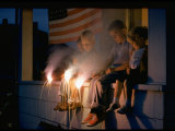 Boys Sitting on Porch Holding Sparklers  with US Flag in Back  During Independence Day Celebration