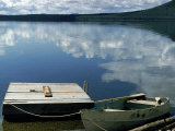 Rowboat Moored at Edge of Lake Showing Reflections of Clouds in Its Still Waters  in New England
